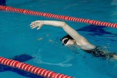 Jeune fille dans les lunettes et style de course de rampement de natation de chapeau dans la piscine d'eau bleue Image stock