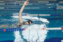 Jeune fille dans les lunettes et style de course de rampement de natation de chapeau dans la piscine d'eau bleue Photo libre de droits