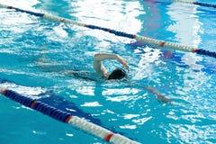 Jeune fille dans les lunettes et style de course de rampement de natation de chapeau dans la piscine d'eau bleue Photo stock