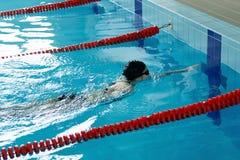 Jeune fille dans les lunettes et style de course de rampement de natation de chapeau dans la piscine d'eau bleue Photos libres de droits