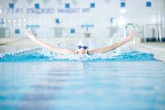 Jeune fille dans les lunettes nageant le style de course de papillon Images libres de droits