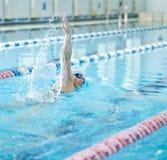 Jeune fille dans les lunettes nageant le style de course de rampement avant Photos stock