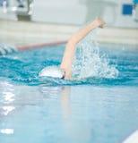 Jeune fille dans les lunettes nageant le style de course de rampement avant Image libre de droits