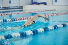 Jeune fille dans les lunettes nageant le style de course de rampement avant Photo stock