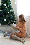 Jeune fille dans un arbre de Noël avec des cadeaux Image libre de droits