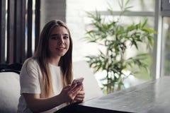 Jeune fille dans un café La fille s'assied sur le divan et parle au téléphone Photo libre de droits