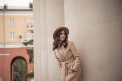 Jeune fille dans un chapeau et un manteau sur le fond des colonnes de théâtre Image libre de droits