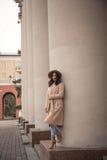 Jeune fille dans un chapeau et un manteau sur le fond des colonnes de théâtre Images libres de droits