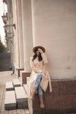 Jeune fille dans un chapeau et un manteau sur le fond des colonnes de théâtre Photo libre de droits