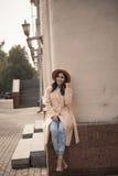 Jeune fille dans un chapeau et un manteau sur le fond des colonnes de théâtre Photos stock