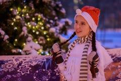 Jeune fille dans un chapeau rouge se tenant à l'arbre de Noël sur le Christ Image libre de droits