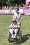 Jeune fille dans un fauteuil roulant avec son aide Images libres de droits