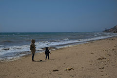 Jeune fille dans un imperméable beige marchant avec un petit fils Images libres de droits
