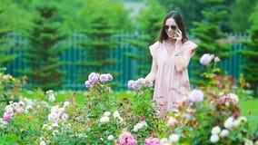 Jeune fille dans un jardin d'agr?ment parmi de belles roses Odeur des roses banque de vidéos