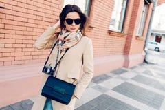 Jeune fille dans un manteau et une écharpe et des lunettes de soleil marchant autour de la ville pendant l'été Images libres de droits