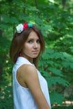 Jeune fille dans une robe blanche avec une guirlande faite main des fleurs Images stock