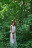 Jeune fille dans une robe blanche avec une guirlande faite main des fleurs Photographie stock libre de droits