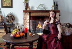 Jeune fille dans une robe de vintage par la cheminée photo stock