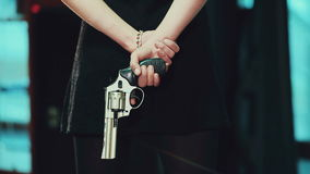 Jeune fille dans une robe noire tenant un pistolet derrière clips vidéos