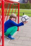 Jeune fille de acroupissement avec la boule dans le but rouge en métal Photos stock