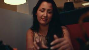 Jeune fille de brune à la table dans le restaurant Tasse de torsion dans des mains Entretien à quelqu'un clips vidéos