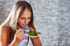 Jeune fille de brune d'adolescent avec de longs cheveux mangeant le dessert vert délicieux de gelée de kiwi sur le fond gris de m images libres de droits