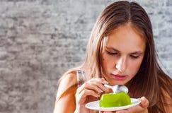 Jeune fille de brune d'adolescent avec de longs cheveux mangeant le dessert vert délicieux de gelée de kiwi sur le fond gris de m photo stock