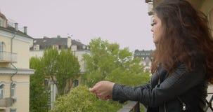 Jeune fille de brune dans la position de veste en cuir sur le balcon appréciant la vue verte spectaculaire de ville banque de vidéos