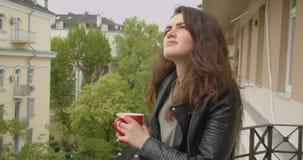 Jeune fille de brune dans la position de veste en cuir sur le balcon appréciant la vue verte spectaculaire de ville et buvant du  clips vidéos