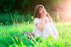 Jeune fille de brune dans la robe blanche se reposant au milieu du champ et des sourires Bonheur, liberté Images libres de droits