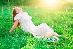 Jeune fille de brune dans la robe blanche se reposant au milieu du champ et des sourires Bonheur, liberté Photos stock