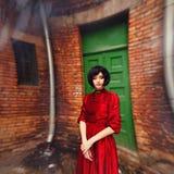 Jeune fille de brune dans la robe rouge romantique de vintage près du mur photos libres de droits