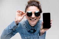 Jeune fille de brune en verres ronds Des poils sont recueillis dans un petit pain Fille avec un téléphone noir Photographie stock libre de droits