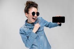 Jeune fille de brune en verres ronds Des poils sont recueillis dans un petit pain Fille avec un téléphone noir Photographie stock