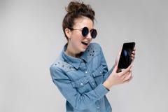 Jeune fille de brune en verres ronds Des poils sont recueillis dans un petit pain Fille avec un téléphone noir La fille regarde Photo libre de droits