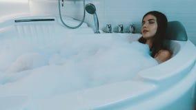 Jeune fille de brune prenant le bain complètement de la mousse dans la salle de bains Détente Sourire banque de vidéos