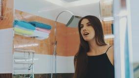 Jeune fille de brune regardant dans le miroir dans la salle de bains Cheveux de contact Vérifiez les dents clips vidéos