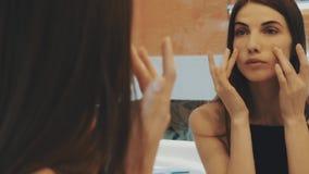 Jeune fille de brune regardant dans le miroir dans la salle de bains Visage de contact, cou Sourire banque de vidéos