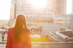 Jeune fille de brune regardant les bâtiments de ville avec la lumière molle du soleil Vue arrière L'espace pour le texte photographie stock