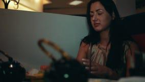 Jeune fille de brune s'asseyant à la table dans le restaurant Sourire thé de boissons parler banque de vidéos