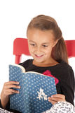 Jeune fille de brune semblant la lecture enthousiaste un livre Photographie stock libre de droits