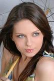 Jeune fille de brunette avec le parapluie dans le blanc Image stock