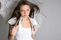Jeune fille de brunette avec le parapluie dans le blanc Photos stock