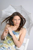 Jeune fille de brunette avec le parapluie dans le blanc Photographie stock