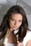 Jeune fille de brunette avec le parapluie dans le blanc Photographie stock libre de droits