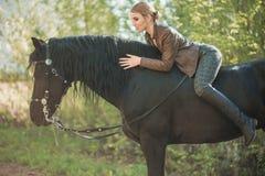 Jeune fille de cavalier avec de longs cheveux se trouvant sur le cou de cheval Images libres de droits