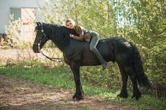 Jeune fille de cavalier avec de longs cheveux se trouvant sur le cou de cheval Photo stock