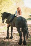 Jeune fille de cavalier avec de longs cheveux se trouvant sur le cou de cheval Photographie stock