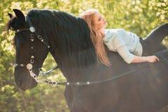 Jeune fille de cavalier avec de longs cheveux se trouvant sur le cou de cheval Image libre de droits