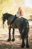 Jeune fille de cavalier avec de longs cheveux se trouvant sur le cou de cheval Photo libre de droits